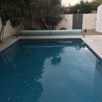 Swimming pool solar cover with roller