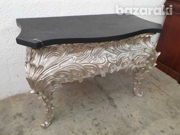 A console table, shaped black top on an eleborate silvered base-1